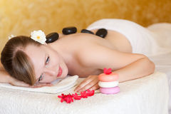 Belle jeune femme obtenant le massage en pierre chaud photos libres de droits