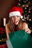 Belle jeune femme ouvrant un cadeau de Noël Photos libres de droits