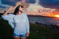 Belle jeune femme par l'océan au coucher du soleil images libres de droits