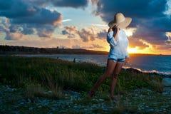 Belle jeune femme par l'océan au coucher du soleil Image stock