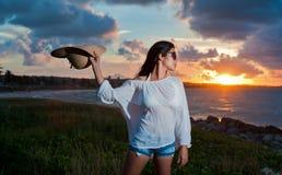 Belle jeune femme par l'océan au coucher du soleil Image libre de droits