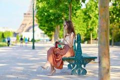 Belle jeune femme parisienne s'asseyant sur le banc Image libre de droits