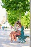 Belle jeune femme parisienne s'asseyant sur le banc Images libres de droits