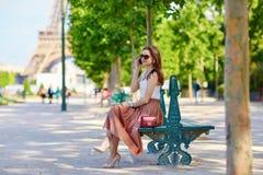 Belle jeune femme parisienne s'asseyant sur le banc Image stock