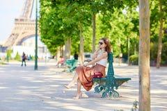 Belle jeune femme parisienne s'asseyant sur le banc Photo libre de droits