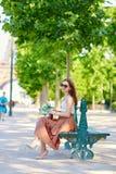 Belle jeune femme parisienne s'asseyant sur le banc Photos libres de droits
