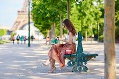 Belle jeune femme parisienne s'asseyant sur le banc Photographie stock libre de droits
