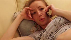 Belle jeune femme parlant au téléphone et décontractée sur le divan indoors clips vidéos