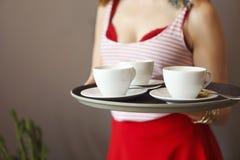 Belle jeune femme portant les v?tements lumineux tenant le plateau avec du caf? image stock