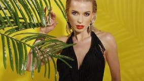 Belle jeune femme posant dans le maillot de bain noir au-dessus du fond jaune banque de vidéos