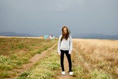 Belle jeune femme posant dans un chemin entre deux champs de blé jour nuageux Roux adolescent photo libre de droits