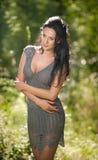 Belle jeune femme posant dans un pré d'été Portrait de fille attirante de brune avec de longs cheveux détendant en nature, extéri Photos stock