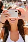 Belle jeune femme prenant des photos avec le téléphone portable. photo libre de droits
