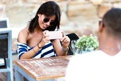 Belle jeune femme prenant la photo de son ami dans la rue Image libre de droits