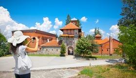 Belle jeune femme prenant la photo du monastère Zica, Serbie Photographie stock libre de droits