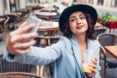 Belle jeune femme prenant le selfie tout en ayant le jus d'orange en café extérieur Photos stock