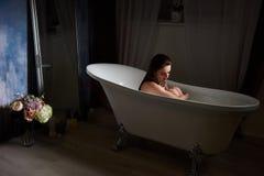 Belle jeune femme prenant le soin au sujet des jambes se situant dans le tube de bain dans la salle de bains images stock