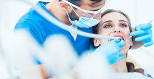 Belle jeune femme recherchant décontractée pendant une procédure dentaire indolore photographie stock libre de droits