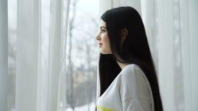 Belle jeune femme regardant l'attente de fenêtre clips vidéos