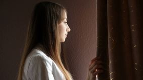 Belle jeune femme regardant la fenêtre banque de vidéos