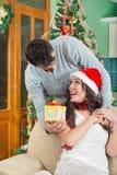 Belle jeune femme regardant le boîte-cadeau et souriant tandis que son garçon Photo stock