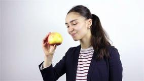 Belle jeune femme reniflant la pomme rouge banque de vidéos