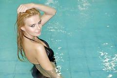 Belle jeune femme restant dans une piscine Images stock