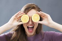 Belle jeune femme riante avec les tranches relevées de citron sur des yeux Image stock