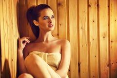 Belle jeune femme rousse détendant dans un sauna finlandais Photo stock