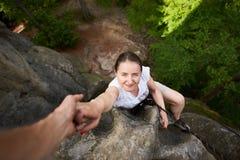 Belle jeune femme s'élevant sur la roche dehors en été Vue sup?rieure Trekking s'élevant de roche de fille heureuse dehors photos libres de droits