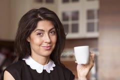 Belle jeune femme s'asseyant à la maison, café potable photographie stock