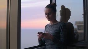 Belle jeune femme s'asseyant à la maison par la fenêtre ouverte avec un sourire regardant le téléphone et introduisant un message clips vidéos