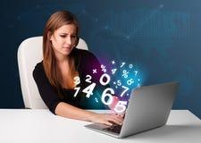 Belle jeune femme s'asseyant au bureau et dactylographiant sur l'ordinateur portable avec Image libre de droits