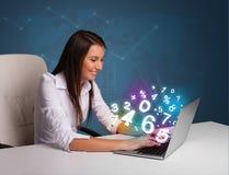 Belle jeune femme s'asseyant au bureau et dactylographiant sur l'ordinateur portable avec Photo libre de droits