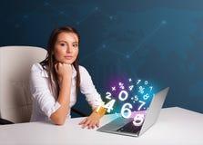 Belle jeune femme s'asseyant au bureau et dactylographiant sur l'ordinateur portable avec Photo stock