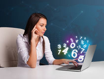Belle jeune femme s'asseyant au bureau et dactylographiant sur l'ordinateur portable avec Photos libres de droits