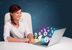 Belle jeune femme s'asseyant au bureau et dactylographiant sur l'ordinateur portable avec Image stock