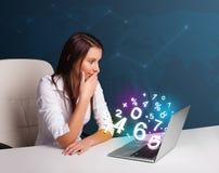 Belle jeune femme s'asseyant au bureau et tapant sur l'ordinateur portable avec Photos libres de droits