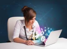 Belle jeune femme s'asseyant au bureau et tapant sur l'ordinateur portable avec Photographie stock libre de droits