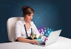 Belle jeune femme s'asseyant au bureau et tapant sur l'ordinateur portable avec Photos stock