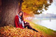 Belle jeune femme s'asseyant dans des feuilles tombées au parc d'automne Photo libre de droits