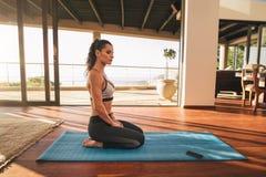 Belle jeune femme s'asseyant dans la pose de yoga à la maison Image stock