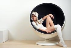 Belle jeune femme s'asseyant dans la rétro chaise à la mode Images stock