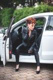 Belle jeune femme s'asseyant dans la voiture blanche avec les portes ouvertes Photo stock