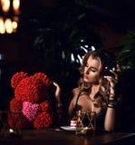 Belle jeune femme s'asseyant dans le restaurant célébrant l'anniversaire avec le gâteau et l'ours rose du cadeau actuel de roses image stock