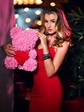 Belle jeune femme s'asseyant dans le restaurant célébrant l'anniversaire avec le gâteau et l'ours rose du cadeau actuel de roses photos stock