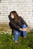 Belle jeune femme s'asseyant dans un mur de briques Photos stock