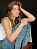 Belle jeune femme s'asseyant dans une chaise avec l'expression réfléchie Photo stock