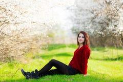 Belle jeune femme s'asseyant devant le tre de floraison merveilleux Image stock