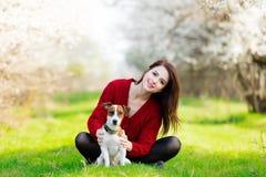 Belle jeune femme s'asseyant devant le tre de floraison merveilleux Photographie stock